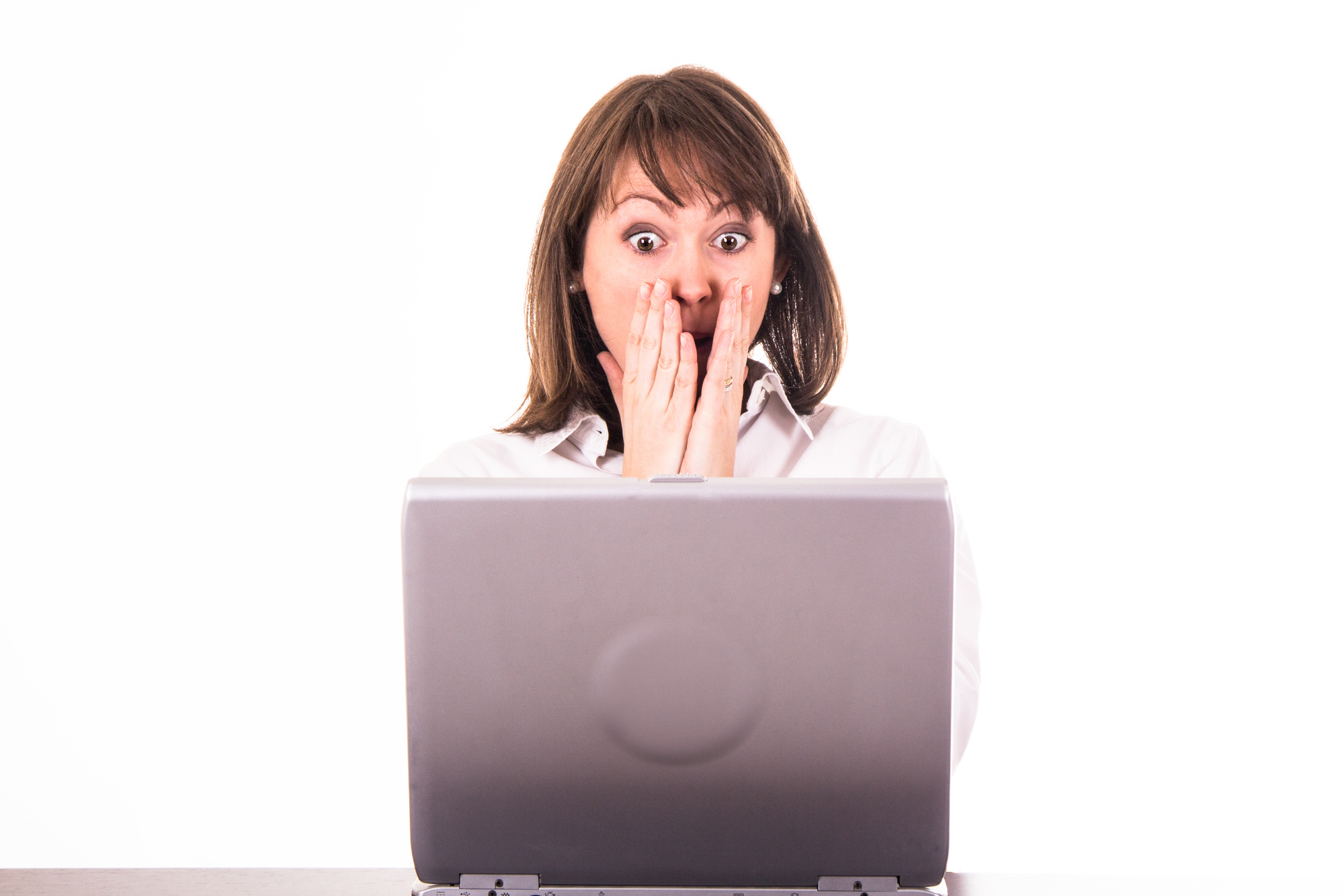 Woman looking at laptop with surprised expression on face