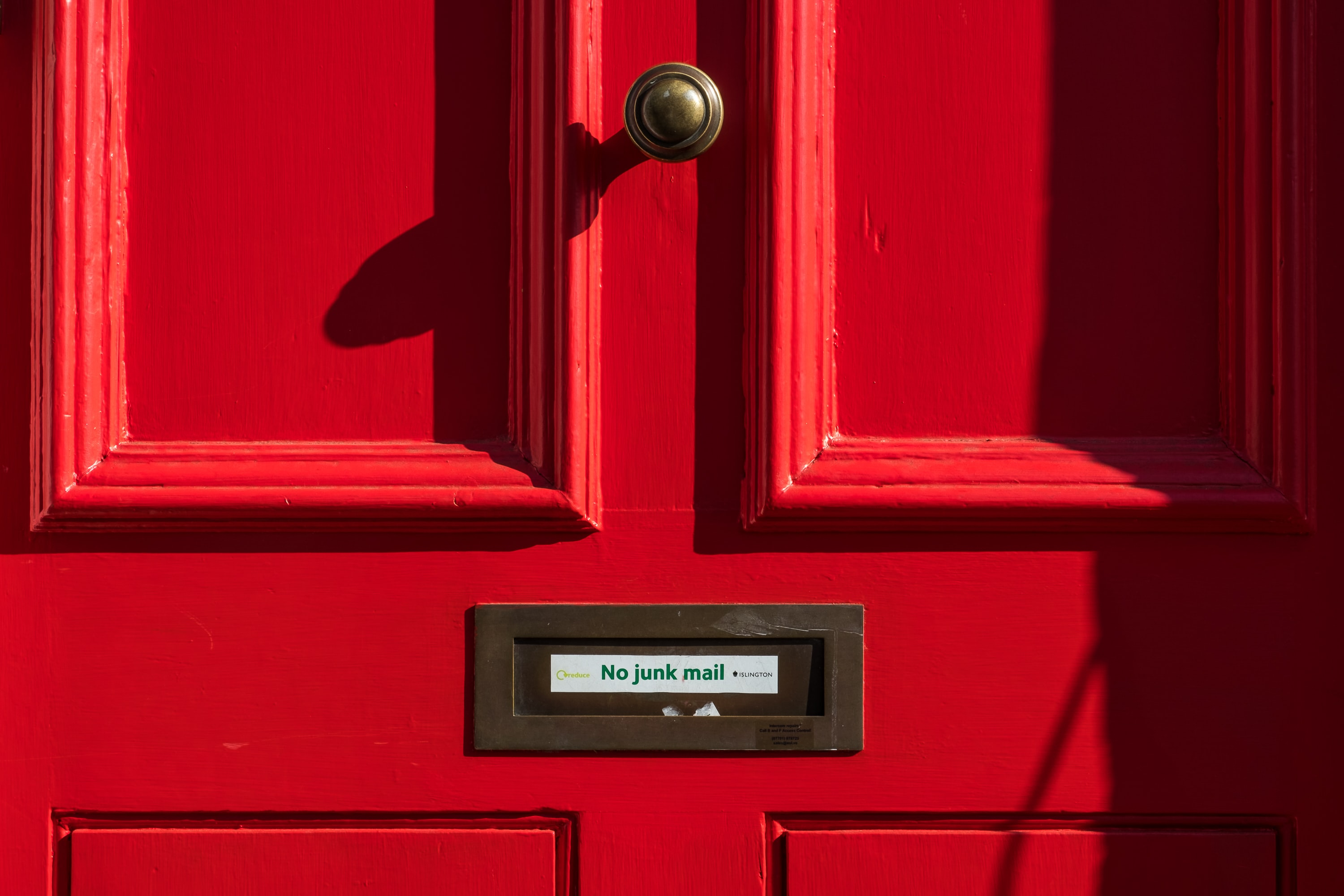 """Closeup of mail slot on red door with sign """"No junk mail"""""""