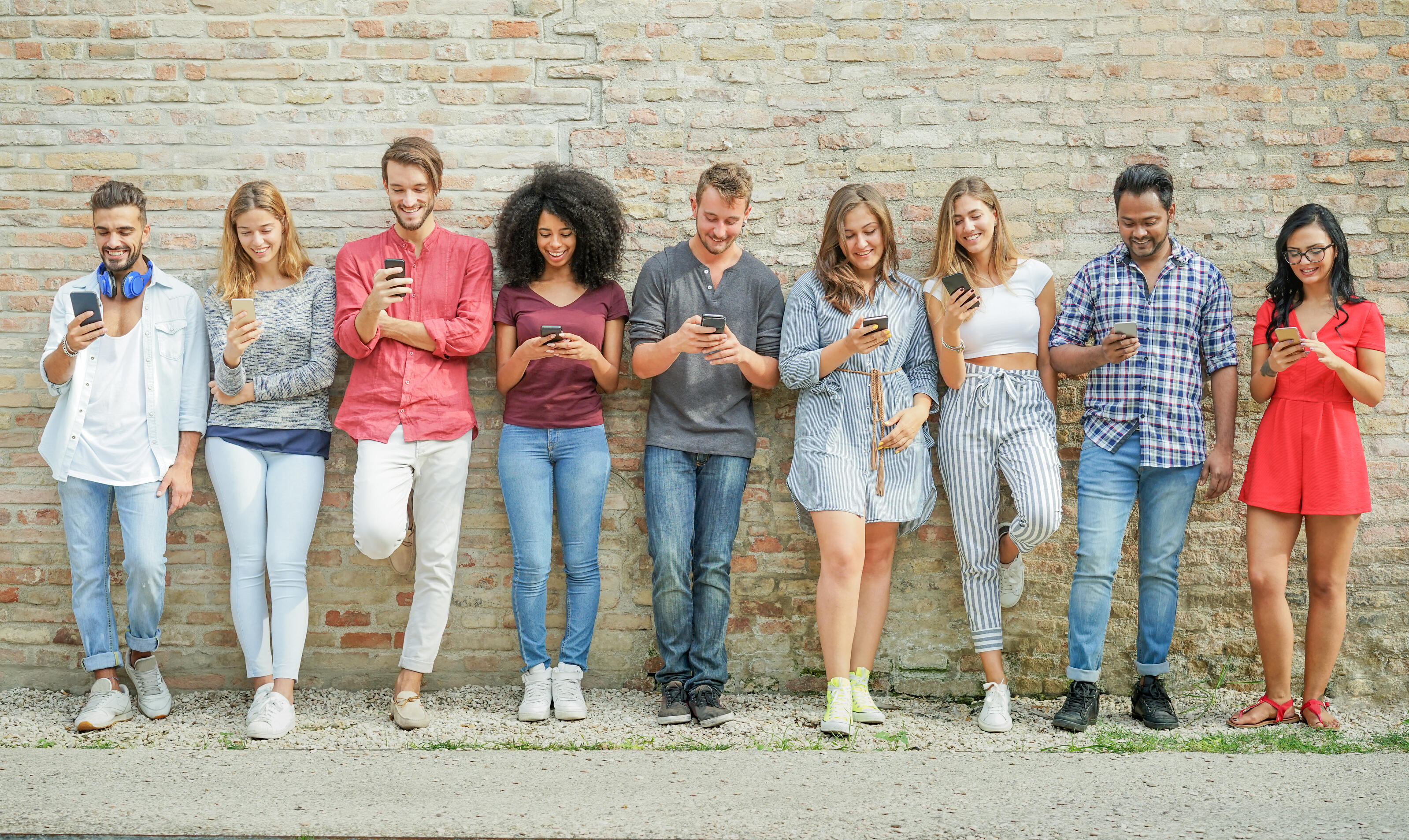 Diverse young people using smartphones outdoors