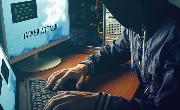 Person wearing hoodie types on laptop while looking at screen with the words Hacker Attack