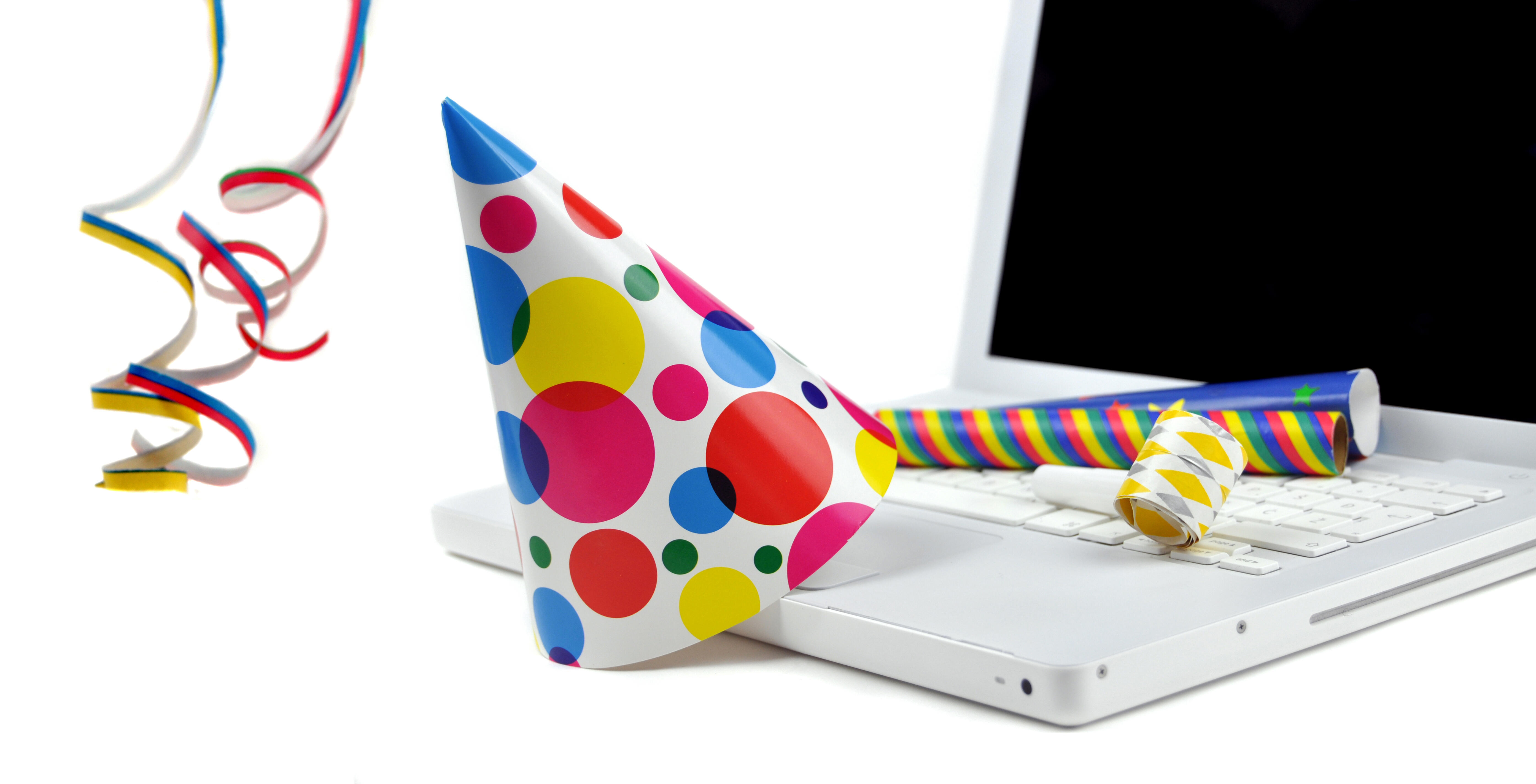 Colorful birthday hat, streamers and noisemakers rest on a white laptop