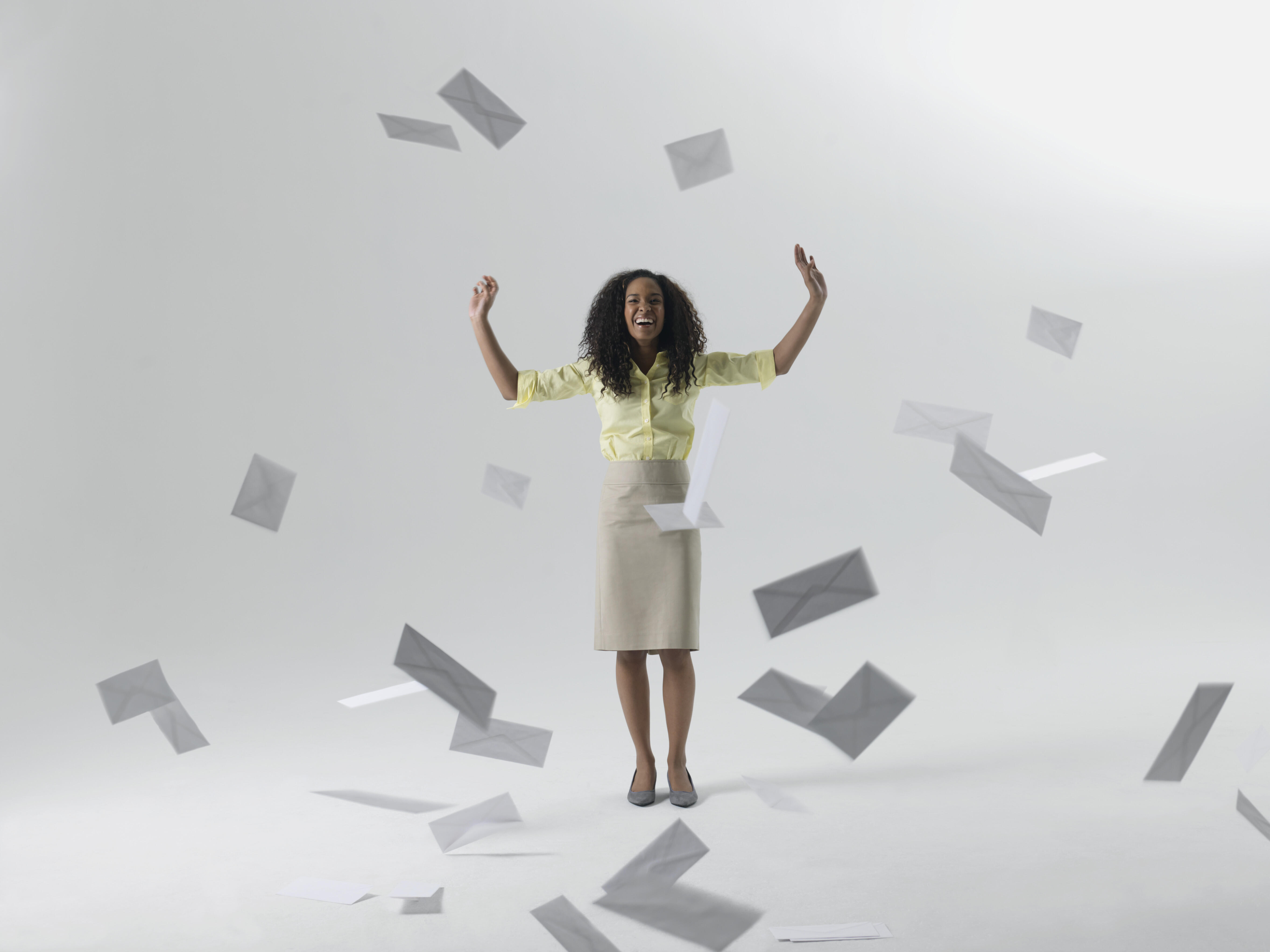 Young Black businesswoman throwing envelopes