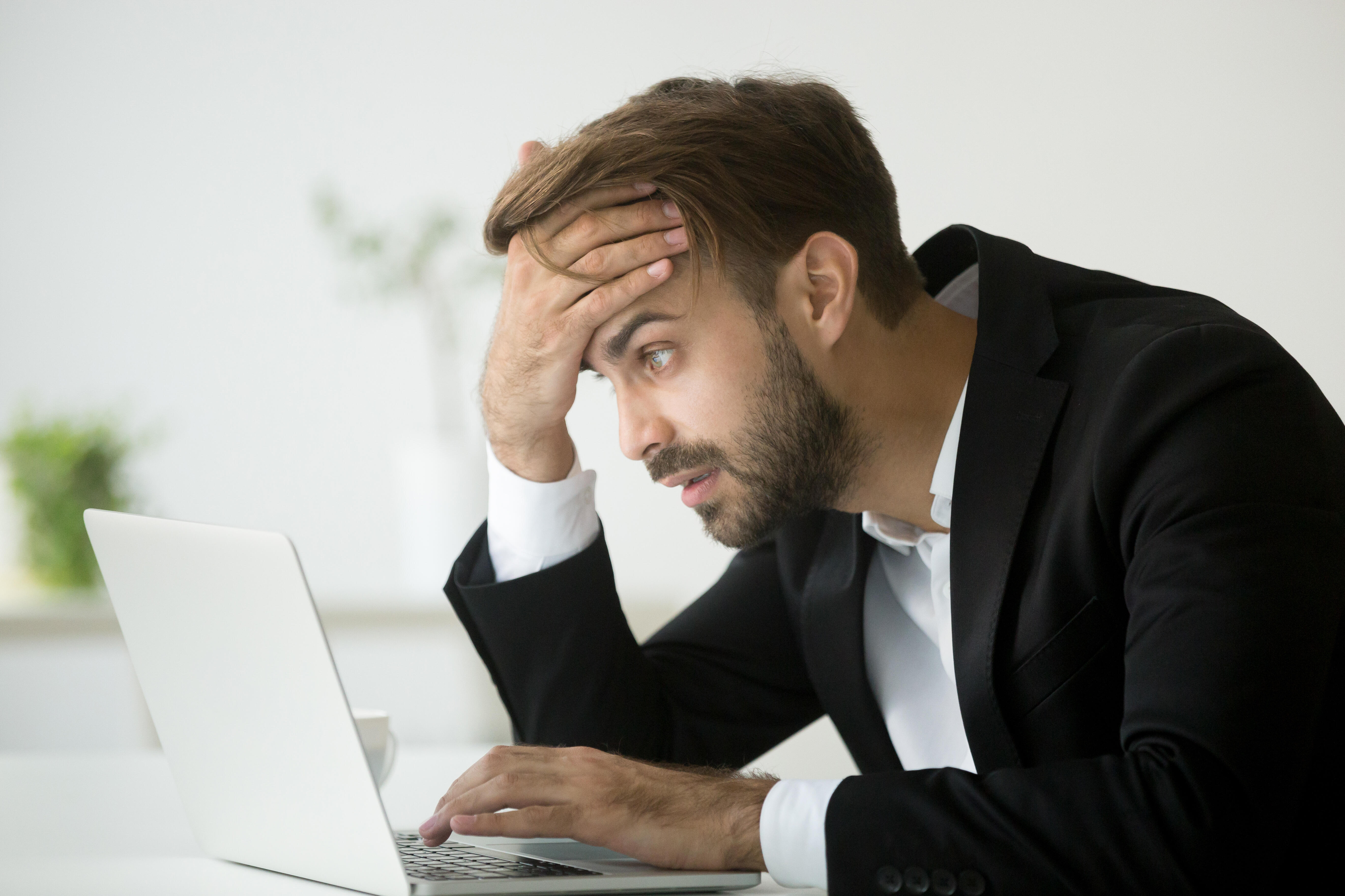 Stressed businessman looks at his laptop