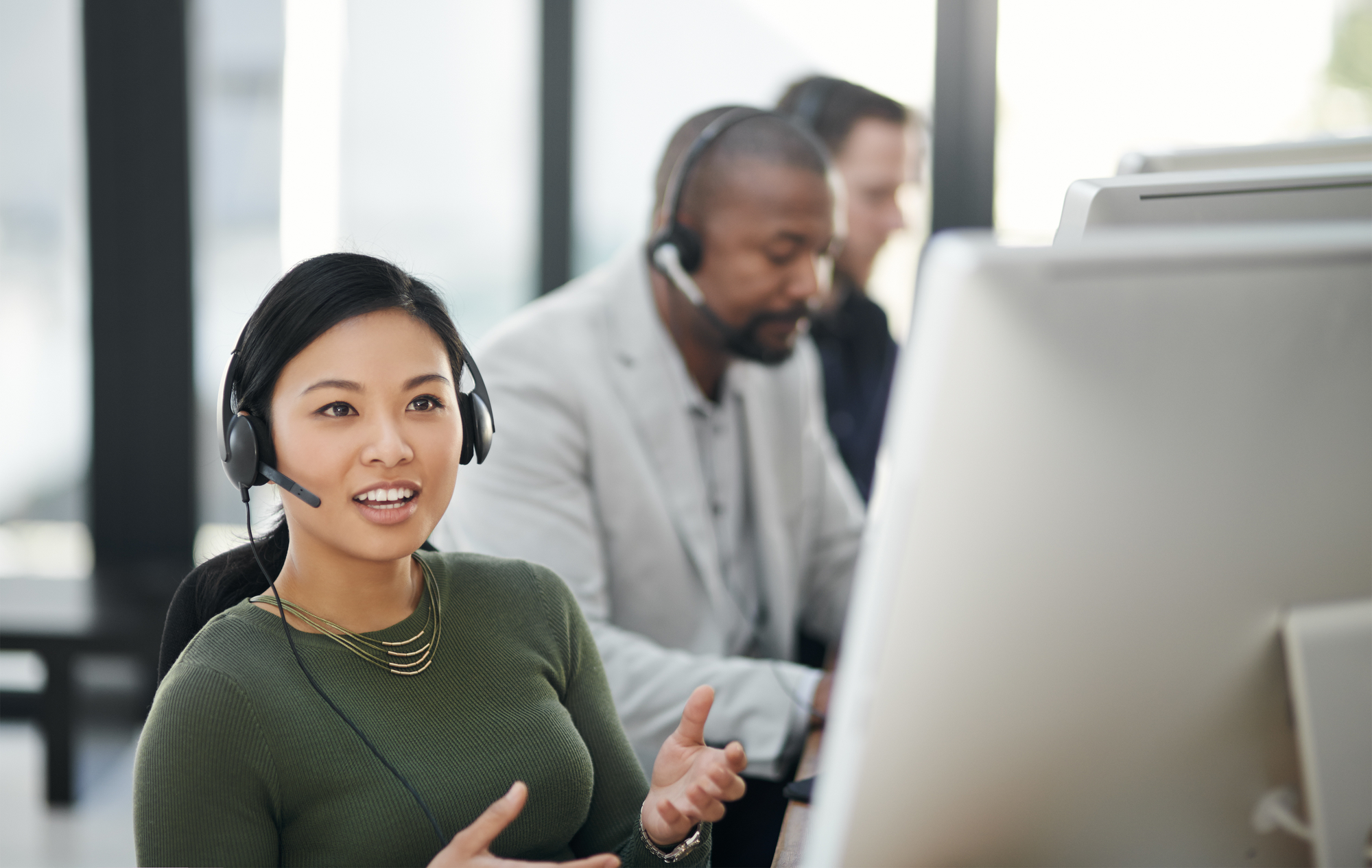 Female customer support agent wearing headset and talking to customer