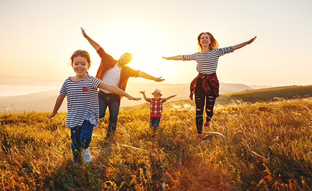 Family of four runs through field of grain at sunset