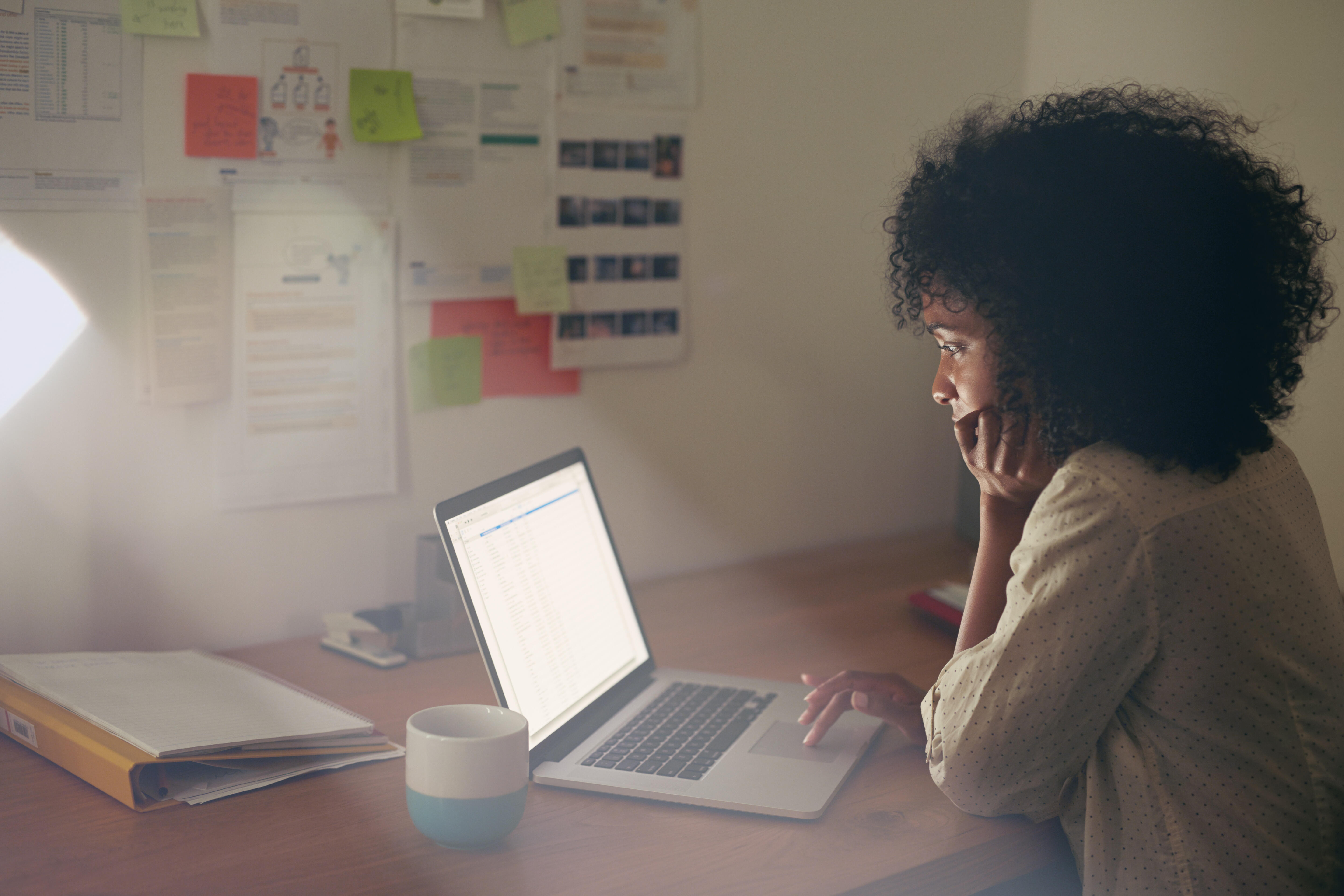 Young women sitting in dark office working on laptop