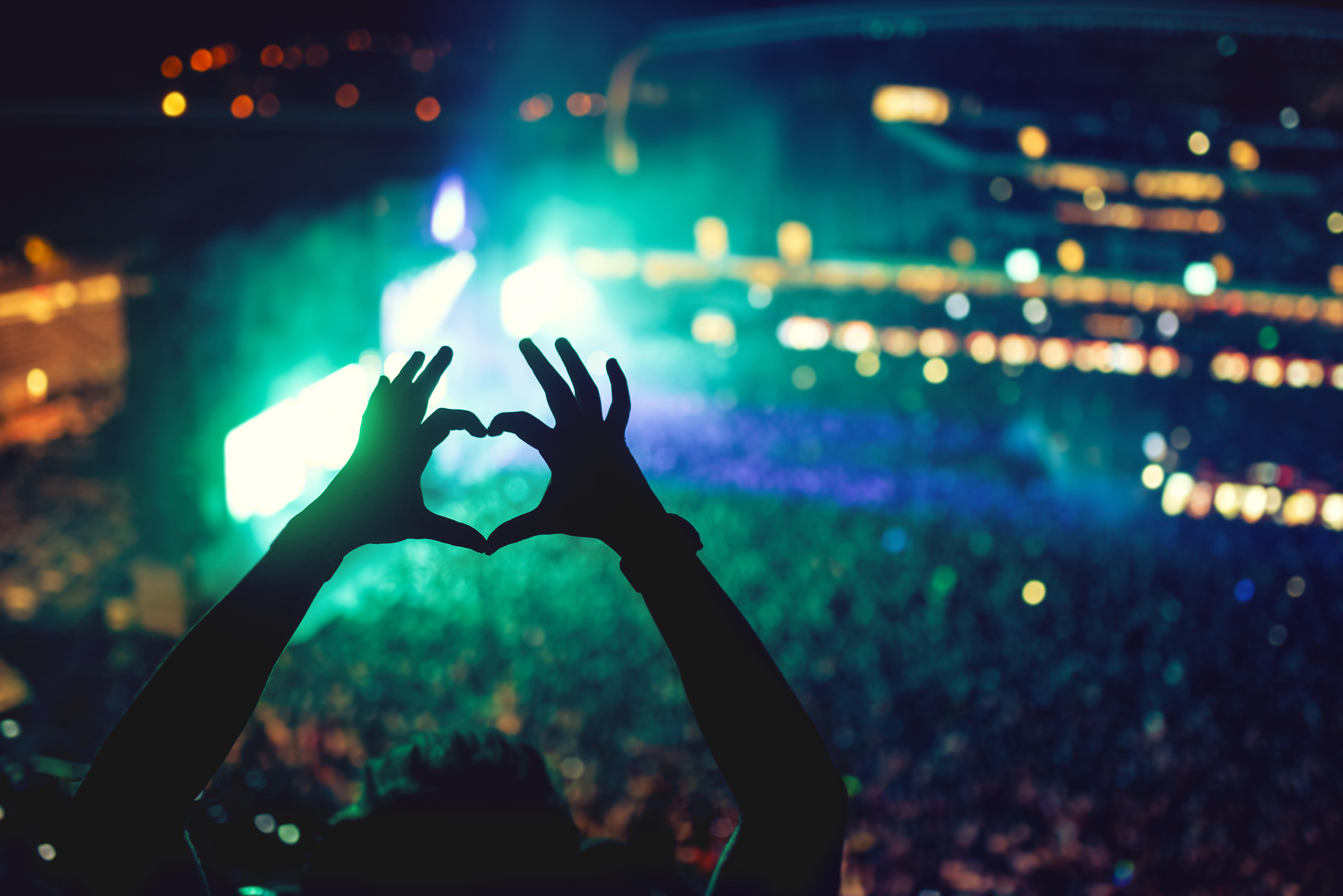 Hands held up in heart shape as silhouette in front of blur of lights in stadium concert