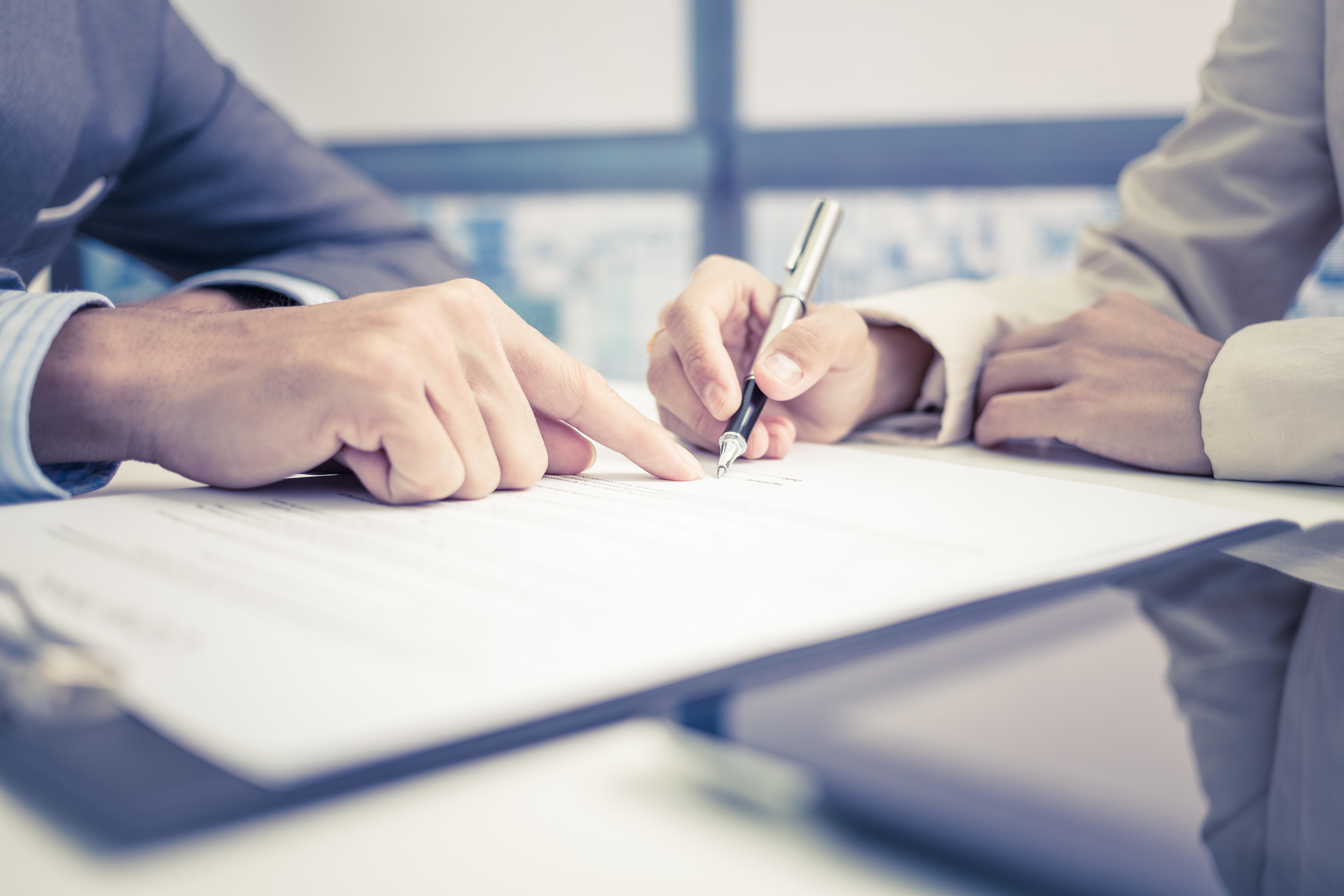 Man's hand pointing at clipboard with document that being signed by woman's hand holding pen
