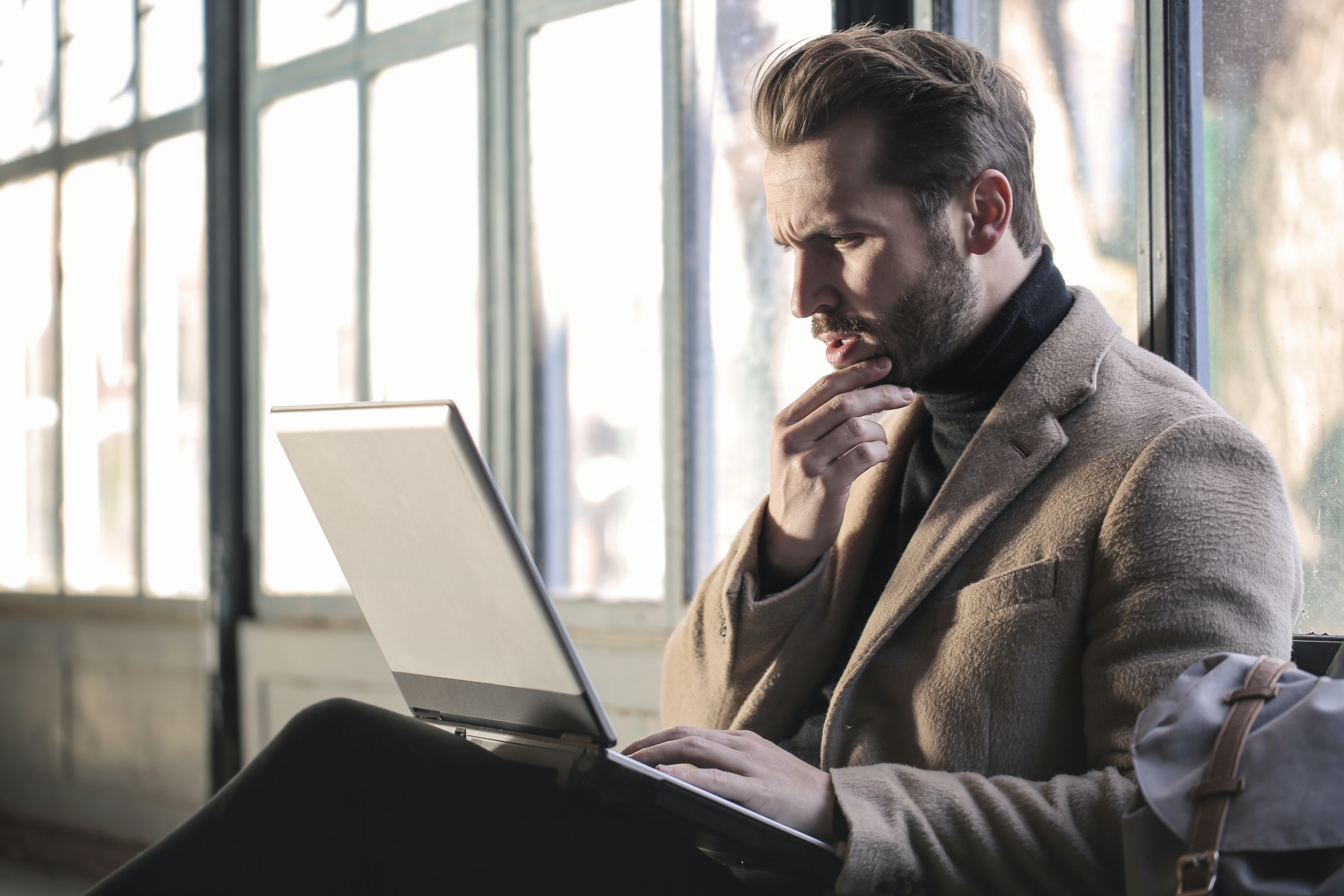 Man with laptop on lap reads screen with surprised expression