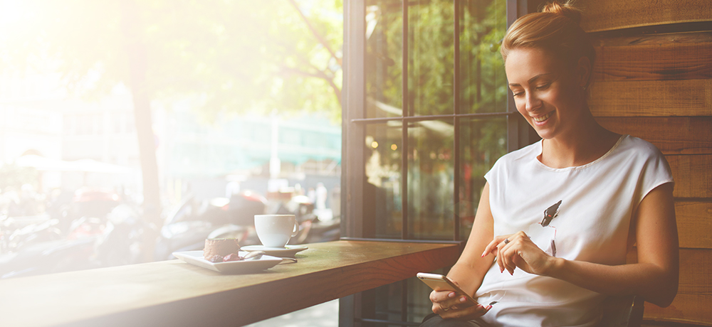Woman in coffee shop reading email on smartphone